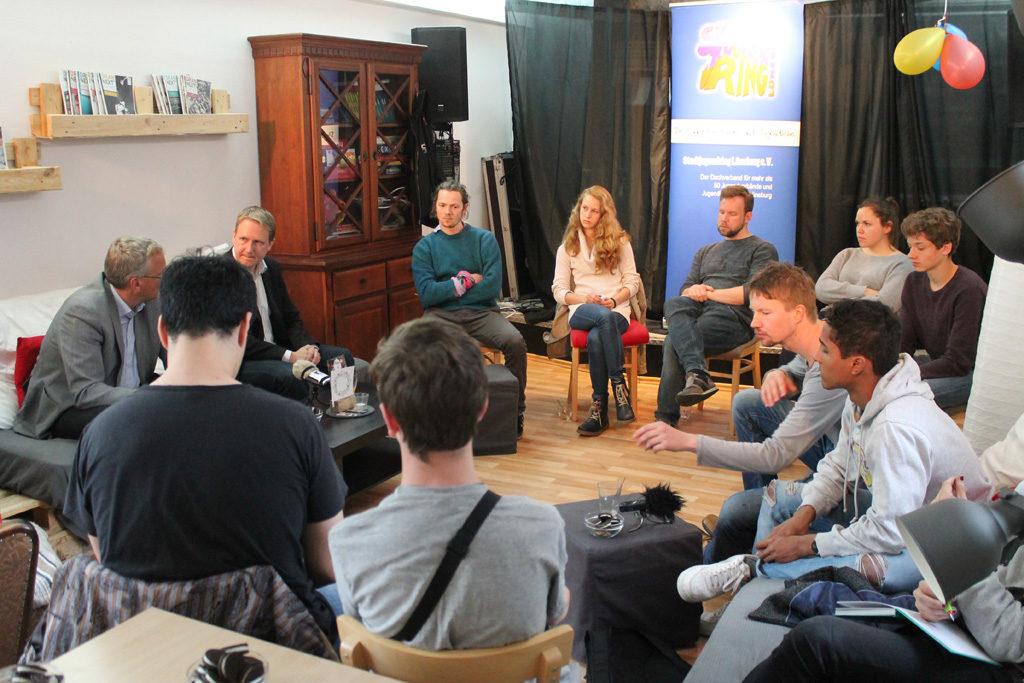 """Jugendliche organisieren Veranstaltungsformat """"Dinner4Two"""" im Rahmen der Landrats-/Europawahl. Eine Runde Jugendlicher sitzt im Kreis mit zwei Politiker*innen, die für die jeweilige Kandidatur auf Landrats-/Europaebene stehen."""